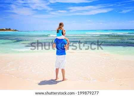 Happy father and his adorable little daughter at tropical beach during summer vacation  - stock photo