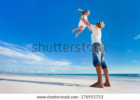 Happy father and his adorable little daughter at tropical beach having fun - stock photo