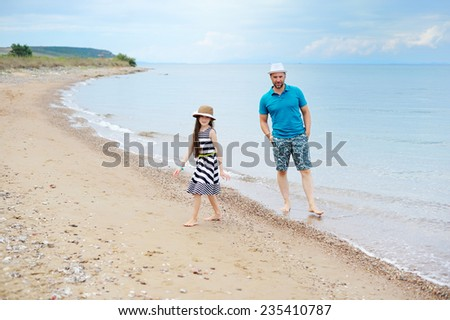 Happy father and his adorable young  daughter at beach having fun - stock photo
