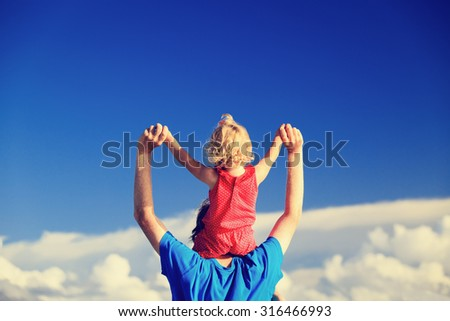 happy father and little daughter on shoulders play on sky - stock photo