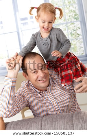 Happy father and little daughter playing at home, little girl climbing on father's shoulder, laughing. - stock photo