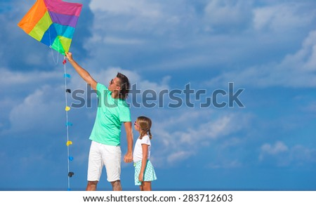 Happy father and little girl flying kite together at tropical beach - stock photo