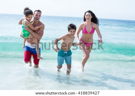 Happy father and mother running with children on sea shore at beach - stock photo