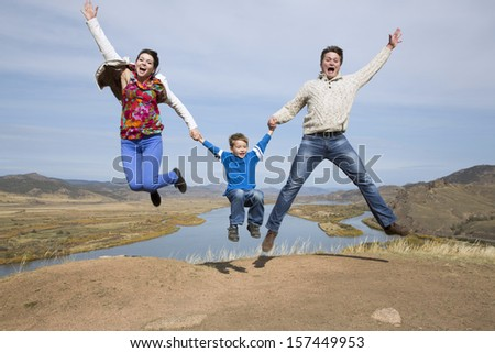 happy father and mother with son jumping on the mountain with lake in the background - stock photo