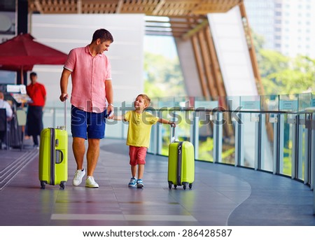 happy father and son are ready for boarding in international airport - stock photo