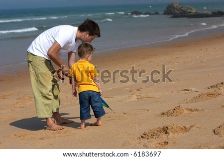 Happy father and son drawing picture on sandy beach - stock photo