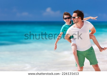 Happy father and son enjoying time at beach during family vacation - stock photo