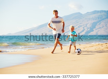 Happy Father and Son Having Fun Playing Soccer on the Beach - stock photo