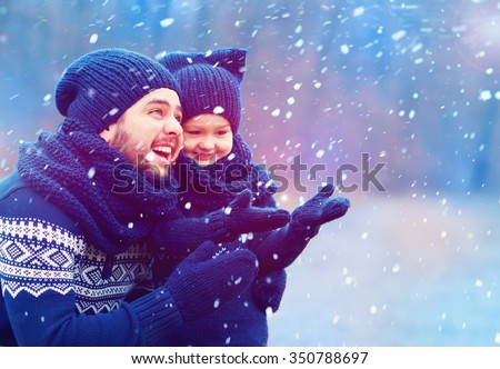 happy father and son having fun under winter snow - stock photo