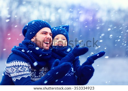 happy father and son having fun under winter snow, holiday season - stock photo