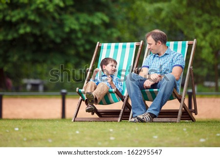Happy father and son having rest in city park on beautiful summer day - stock photo
