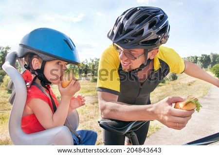 Happy father and son is eating lunch (snack) during bicycle ride. Child (boy) and man have biking helmets. The son is in the bicycle chair (seat). Caucasian smiling male models. Travel concept.  - stock photo