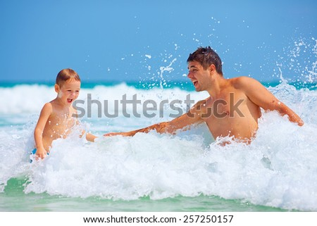 happy father and son jumping in waves, summer vacation - stock photo