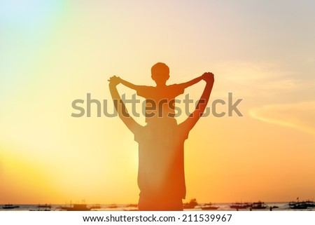 happy father and son on sunset beach - stock photo