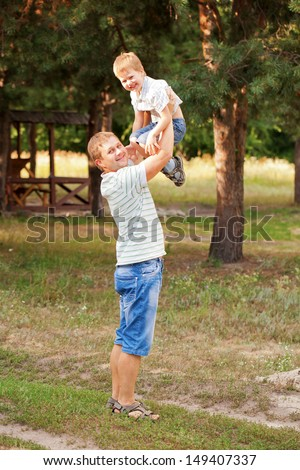 Happy father and son outdoors. Daddy raising up the child. - stock photo