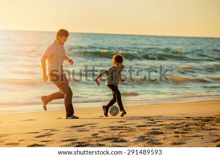 Happy father and son play soccer or football on the beach on sunset having great family time on summer holidays. Lifestyle, vacation, happiness, joy concept - stock photo