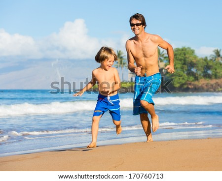 Happy father and son playing and running together at beach, carefree happy fun smiling lifestyle - stock photo
