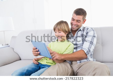 Happy father and son playing game on digital tablet at home - stock photo