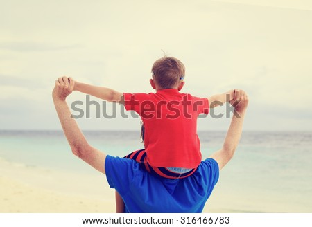 happy father and son playing on sea vacation - stock photo