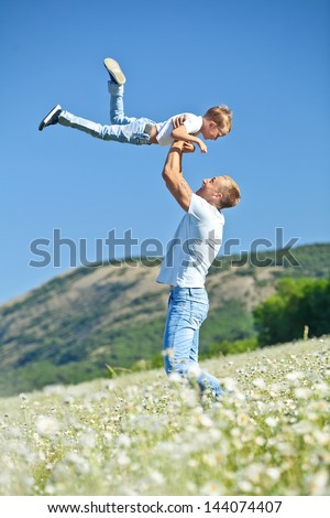 happy father and son playing on sky background - stock photo