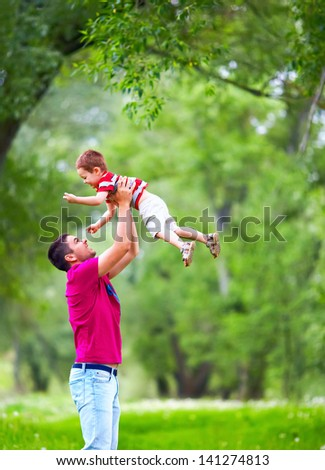 happy father and son playing outdoors in spring forest - stock photo