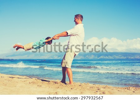 Happy father and son playing together at the beach. Fun vacation summer lifestyle. - stock photo