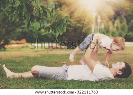 Happy father and son playing together having fun in the autumn park on a warm sunny day. Family and love concept. - stock photo