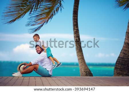 happy father and son playing together near the seaside - stock photo