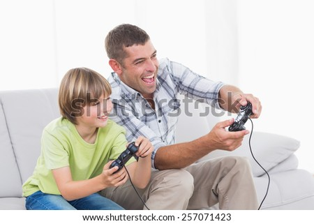 Happy father and son playing video game on sofa - stock photo