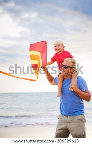 Happy father and son playing with kite at the beach at sunset - stock photo
