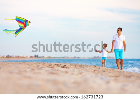 happy father and son playing with kite on summer beach - stock photo