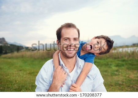 Happy father and son portrait playing together having fun - stock photo