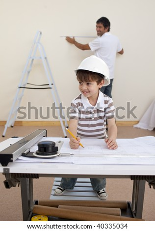 Happy father and son studying architecture at home - stock photo