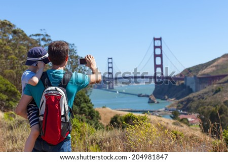 happy father and son taking picture of golden gate bridge in san francisco, travel and technology concept - stock photo