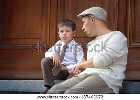 Happy father and son talking and having rest on beautiful summer day - stock photo