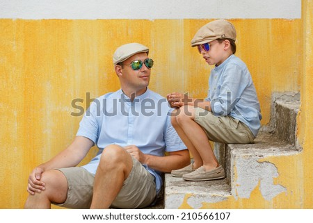 Happy father and son talking and having rest outdoors in city - stock photo