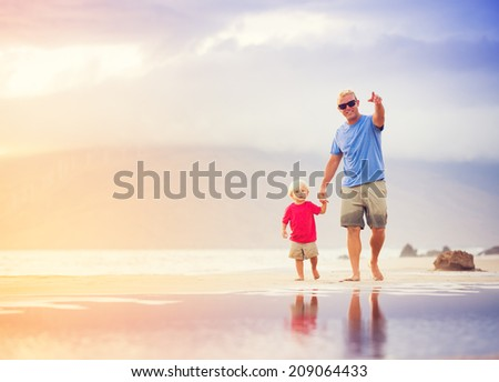 Happy father and son walking on the beach at sunset holding hands - stock photo