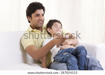 Happy father and son watching television - stock photo