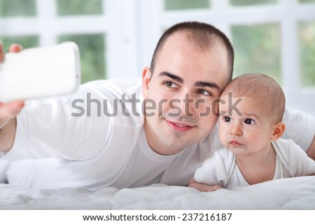 Happy Father and son with mobile taking photo of themself - stock photo