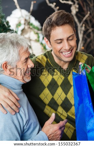 Happy father and son with shopping bags in Christmas store - stock photo