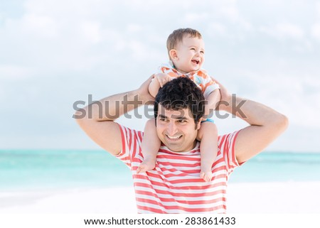 Happy father carries son on his shoulder, having vacation on Maldives - stock photo