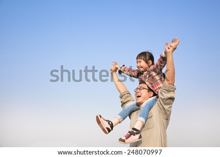 happy Father carrying his daughter on shoulders with blue sky background - stock photo