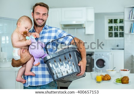 Happy father carrying playful son while holding basket by table in kitchen - stock photo