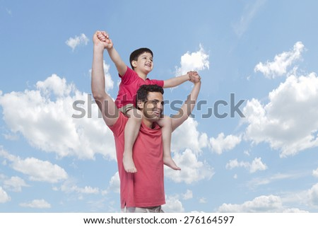 Happy father carrying son on shoulders against cloudy sky - stock photo