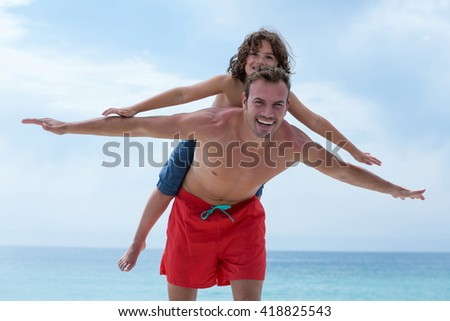 Happy father carrying son while enjoying at beach - stock photo