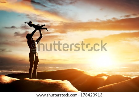 Happy father celebrating his little child by the seaside at sunset, summer time. Birth, new born, fatherhood concepts - stock photo
