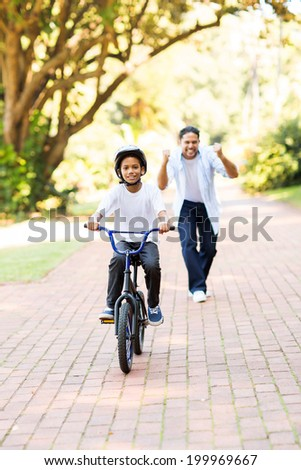 happy father cheering when his son can ride a bike on his own for the first time - stock photo