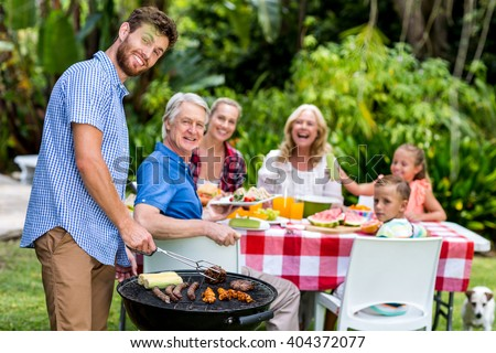 Happy father grilling food on barbeque at yard - stock photo
