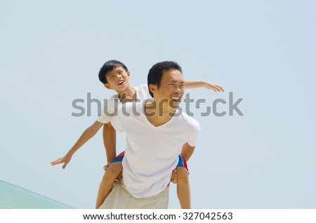 Happy father holding her son on the beach   - stock photo