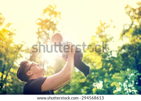 happy father holding little kid in arms, throwing baby in air. concept of happy family, vintage effect against light  - stock photo